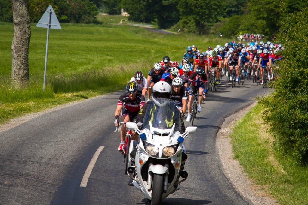 Cykelryttere på landevej med eskorte