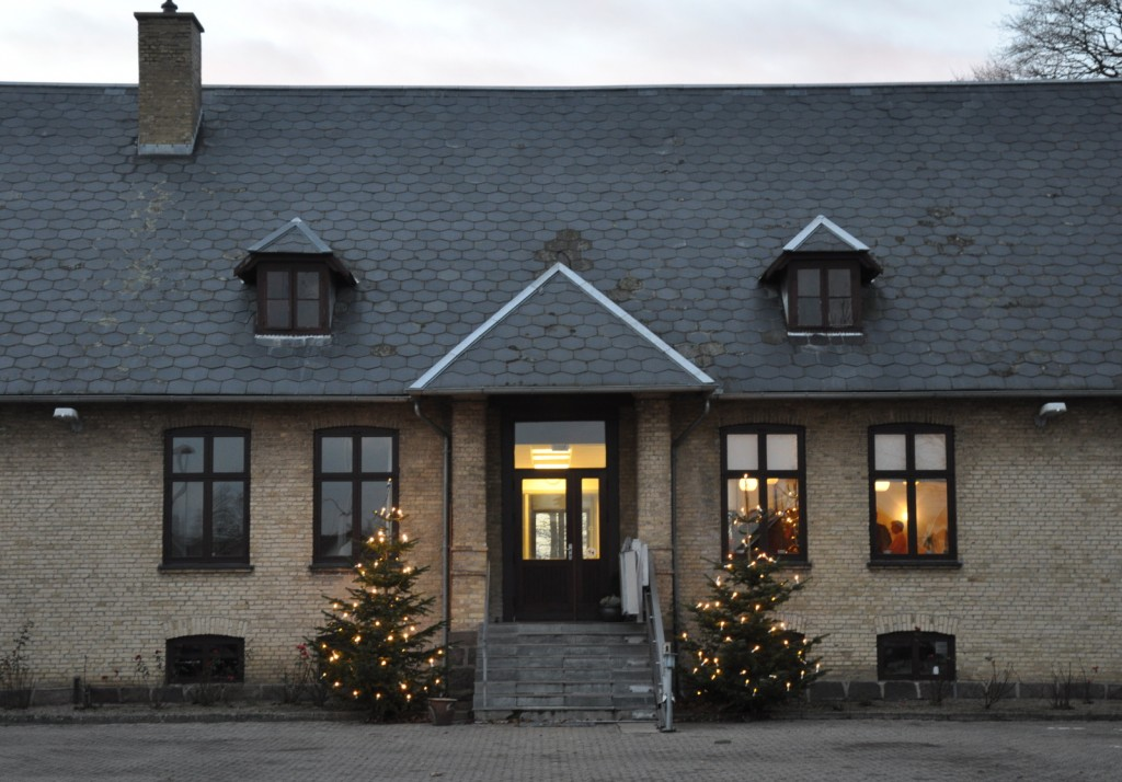 Hovedindgangen med juletræer med lys på begge sider.